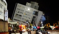 Rescuers are seen entering a building that collapsed onto its side from an early morning 6.4 magnitude earthquake in Hualien County, eastern Taiwan, Wednesday, Feb. 7 2018.  Rescue workers are searching for any survivors trapped inside the building. (AP Photo/Tian Jun-hsiung)/2018-02-07 04:27:57/